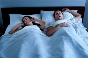 a woman plugging her ears while her husband snores