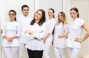 dental team members standing together and smiling