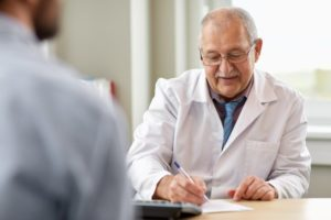 a doctor writing out a physician referral for a patient