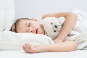 a young boy asleep on his side holding a teddy bear and breathing with his mouth open