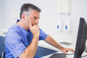 a male dentist sits at a computer and analyzes the information on the screen