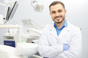 a male dentist smiles while wearing a lab coat and gloves in preparation for seeing a patient