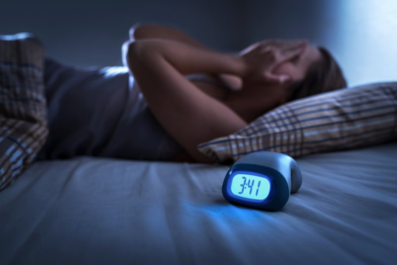 a person lying in bed awake while the alarm clock reads 3:41 a.m.