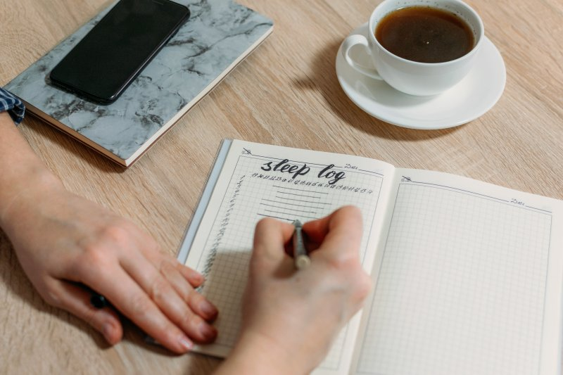 an up-close look at a person's sleep log as well as a cup of tea, cell phone, and notepad