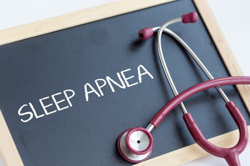 """a small chalkboard with the words """"Sleep Apnea"""" on it and a red stethoscope"""