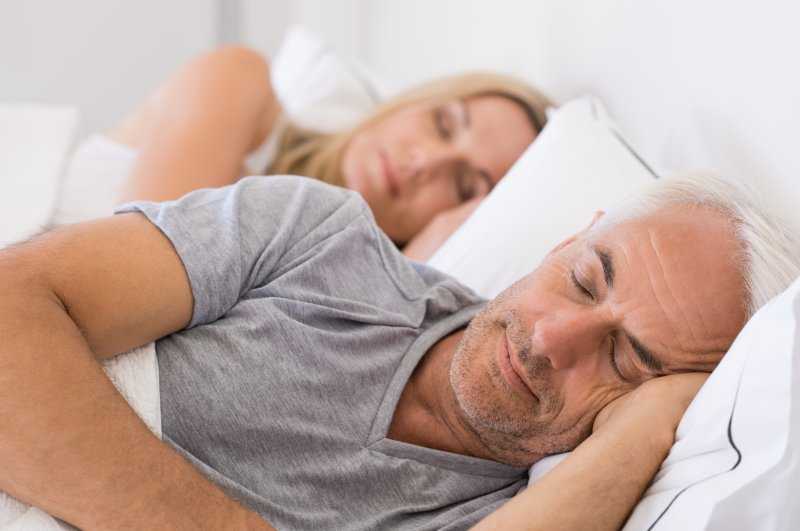 an older man and his wife lying in bed asleep