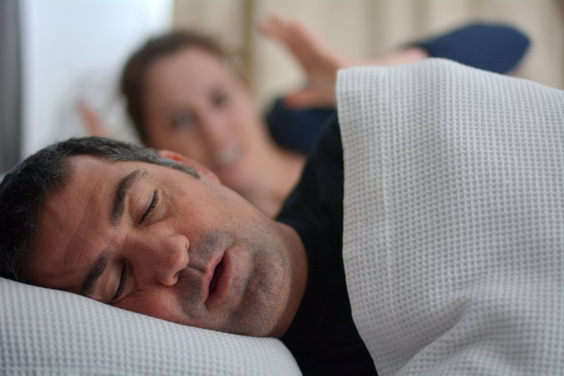a middle-aged man asleep and snoring while his wife acts frustrated in the background